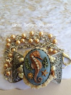 FUF 4/17 A B'sue Seahorse is painted using alcohol inks and is mounted on a B'sue large bow .. pearls and B'sue silver chain comepletes this bracelet .. Jann Tague Clever Designs .. https://www.facebook.com/JewelsByJann