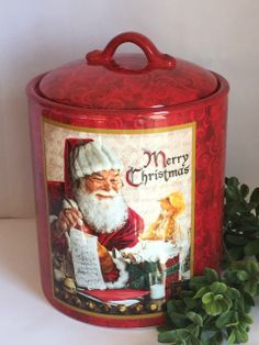 "The lux of the red that enrobs this canister is what drew our eye to it first. To be simple.  It is just delicious.  The ornate scrolled handle and the image of Santa checking his list conjure up feelings of Christmas's gone by. This canister would make for a great cookie jar, or storage piece for holiday baubles that are sure to present themselves this holiday season! Handwash only/FDA approved. Ceramic.  Dimensions: 8 1/2""H X 6 3/4""W X 6 3/4""D X 5 1/4"""