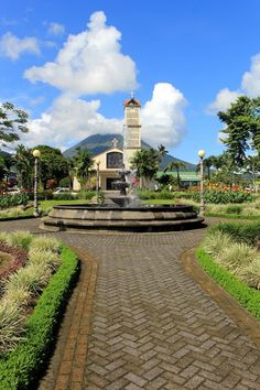 The park and church at La Fortuna, Costa Rica. This local town is a popular spot for tourists to explore the Arenal area, and the view of the volcano is always amazing. http://mytanfeet.com/cities-costa-rica/la-fortuna-de-san-carlos-a-real-fortune-in-nature/