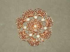 Flor em croche de fio de metal,  cobre esmaltado em dourado, bordado com pérolas.