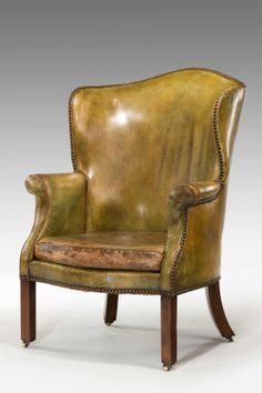 A George III period Library Wing Chair with a barrel form arched top back, upholstered in mellow pale green leather, with close brass nailed edges, the serpentine fronted seat with a squab on mahogany block legs and brass castors, apparently with an old indistinct ink label pasted to the top arched rail..'A Tub Easy Chair with foot(?) board 12 inches from...15 inches high above the foot board. Mrs Cotsford(?) Ravenhill'
