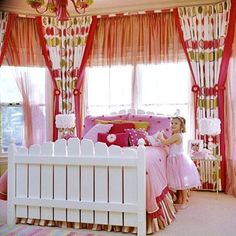A bank of windows frames a pretty picket-fence bed. Surrounded by colorful curtains, the bed is the room's focal point. Sunlight streams in to illuminate the space, but heavy curtains can be drawn to block out the light for nap time. Although a double bed might look oversized now, it will accommodate a growing child in later years, making it a strategic long-term investment. Copyright &copy 2009 Meredith Corporation.