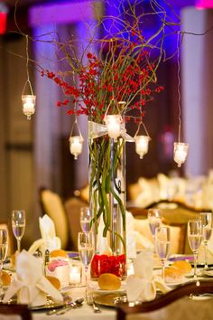 Red floral centerpiece with candles hanging.  Interesting idea...substitute the berries for a red flower version