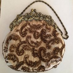 Beautiful Vintage Beaded Evening Bag This a a beautiful taupe and brown beaded vintage evening bag. Ornate metal scrolling across top. Metal snap closure. Inside is taupe silky material with slip pocket. Excellent clean condition inside and out. Beautiful beading. Smoke free home. Bags