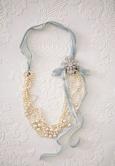 Fold beads in half, tie ribbon, ( to the length you want around your neck ) add charms, a brooch or a flower to hide fold. Gorgeous!