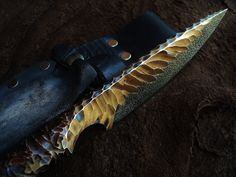 "The Spear Point by Sage Blades. Length: 11 inches O1 Tool Steel ""Stone-Age"" and ""micro-peen'd"" textures Heat oxide coloration (from heat treatment) Kydex and Leather Sheath"