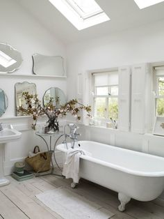 all white bathroom with clawfoot bathtub, collected vintage mirrors, and double sky lights