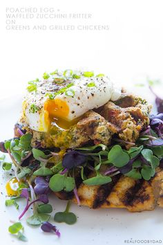 poached egg & waffled zucchini fritters on greens and grilled chickens