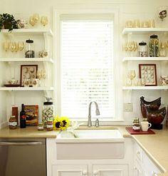 Sugarberry Cottage -Open shelving flanking the kitchen window displays wine glasses and decorative accessories. Counterspace is generous enough to display cookbooks and canned produce from Lowcountry farms.