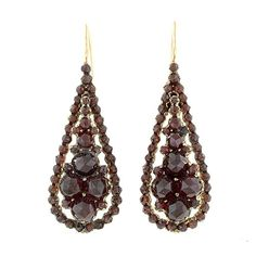 Late Victorian Bohemian Garnet Earrings. Bohemian (pyrope) garnet drop earrings suspended from 14K yellow gold wires. The traditional rose-cut garnets are prong-set in gilded brass and designed in a very flattering tear-drop style. Circa 1900.