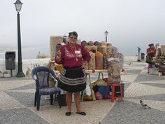 A woman in the traditional dress selling beans, dried fruits and other assortments. Nazare