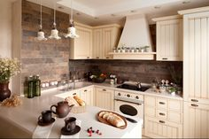 Интерьер кухни радует глаз светлой нарядной мебелью и ажурными подвесными светильниками.