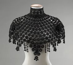 ~Jet-beaded silk crocheted pelerine (cape), American, ca. 1890. This is a nice example of decorative beadwork accessories and garments which were considered high style in the 1880s and 1890s. The pendant points and ball fringe would make a lively, glittering vision in motion, calling attention to the wearer~  #1880 #fashion