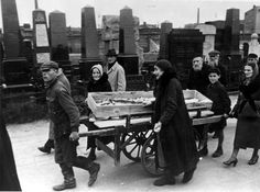 Warsaw, Poland, A coffin on a wagon in the cemetery, surrounded by people crying.