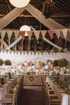 rustic wedding barn styling including draping, bunting, pom poms and fairy lights / http://www.deerpearlflowers.com/unique-bunting-wedding-ideas/2/