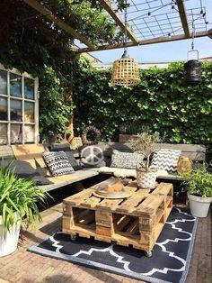une table basse exterieur à roulettes d'aspect brut réalisée avec deux palettes superposées, salon de jardin réalisé entièrement en palettes