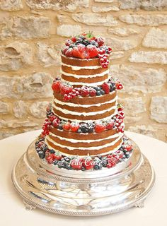 A lemon drizzle, vanilla and carrot and walnut naked cake, decorated with fresh fruits and currants.   At Winkworth Farm for Rachel and Peter's Wedding.