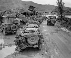 A long line of jeeps waiting to be ferried across the Kumho-gang River cause a traffic jam on the way to the front in Korea. 16 Sep 1950.