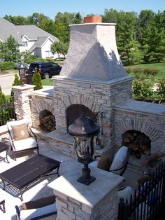 A beautiful outdoor fireplace with large sitting area.
