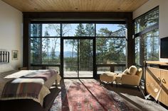 image of contemporary interior design, master bedroom looking out windows to forest view, wilson, wy