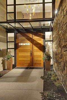 mix of wood, steel and stone at entry... front glass porch and nice door... Expanding ceiling height if garage gets moved in front... like the warm striped/varied wood tones. like the weight that the side piece adds to entry.... door and a half front door... works well with the front door... Idea for 'H' style home entry...