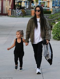 Mama's girl: Penelope stayed close to her mom while looking cute in a black ensemble with black loafers