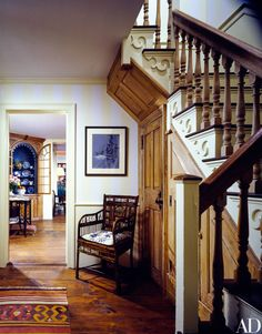 Dominick Dunne's home in Connecticut. The staircase, from an old Connecticut house, was reassembled in the entrance hall. A chinoiserie bamboo armchair is below a charcoal line drawing. Through the doorway is a circa 1780 shell-carved corner cupboard that holds an assortment of Canton porcelain.