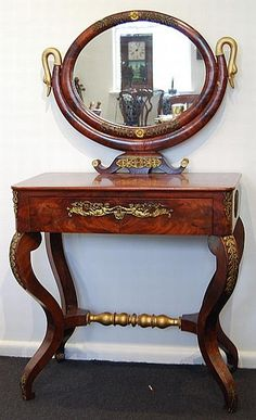Empire style mahogany dressing table, c1910 the central oval mirror flanked by twin scrolled supports having gilt swan terminals; the lower part with rectangular top leading to a central long drawer on cabriole supports with applied gilt metal moldings and United by a gilt stretcher. Width 73 cm. Depth 44 cm. Height 140 cm