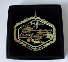 Tennessee State Brass Ornament Black Leatherette Gift Box - As the music capital of America, the banjo and guitar symbolize Nashville's successful music industry and history.  Shiloh, Memphis, Chattanooga and Gatlinburg are all represented.  The Great Smoky Mountains are pictured, most popularly known as home to many black bears.  Perfect gift for music lovers.