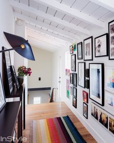 In the upstairs hallway, a wall filled with framed artwork and a rainbow-striped runner pack plenty of visual interest.  Source: Dean Kaufman for InStyle