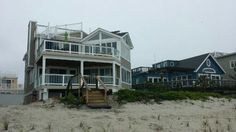 Beautiful 3 story deck with glass railing #shorehouse #glassrailing #customdecks allvinylfencing.net