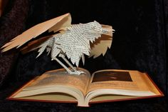 "Edgar Allen Poe Book Sculpture  by ~wetcanvas ©2012   The raven gazes at his creator in this book sculpture. The book used is ""The Road to Greatness"", 1947, a collection of biographies. The biography of Poe tells of the hardships that took him from a happy, well-to-do youth to a macabre author. The raven is wired through the book for stability and also has bendable wings. The illustration he perches over is an engraving of a 19 year-old Poe."