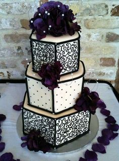 Three tier hexagonal wedding cake in ivory and black with dark purple flowers.JPG