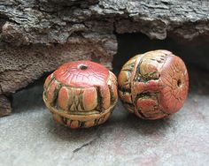 A pair of barrel beads with organic patterns in shades of red-orange, gold and black    Approximately 15mm diameter, 12mm hole to hole. Hole .5mm.