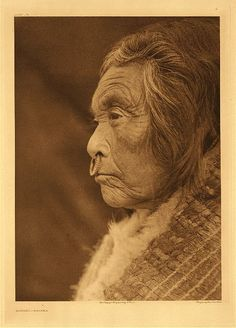 "Haiyahl – Nootka, 1915. Photogravure. Curtis Caption: ""A Nootka woman in profile, with a shell nose-ring and fur-edged bark blanket."""