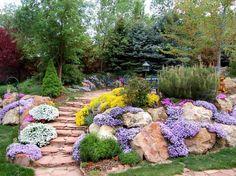 jardin en pente, marches en pierre naturelle, plantes et fleurs multicolores