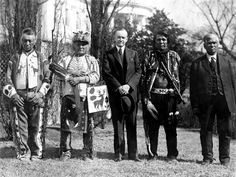 President Calvin Coolidge with four Osage Indians; the White House is in the background. The Osage, who speak a Sioux language dialect, formerly inhabited what is now Missouri and hunted in what is now northern Arkansas. On June 2, 1924, President Coolidge signed a bill granting Native Americans full citizenship.