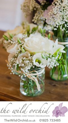 A trio of clear glass jam jars with natural raffia ribbon filled with delicate white flowers with touches of blue.: