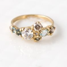 This solid 14k yellow gold ring is the only one of its kind, with a cluster of sparkling gems carefully chosen and hand-set by Melanie here in our studio. Together, the gemstones create a pale sea gla