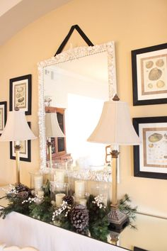 entry table w/ varying sizes of hurricanes w/ greens/pinecones flanked by buffet lamps
