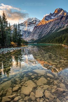 Mount Edith Cavell reflected in the calm river at sunrise in the rocky mountains of Jasper National Park, Alberta, Canada.
