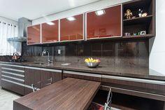 Os móveis da cozinha receberam MDF Ébano Grigio com portas de alumínio e vidro em nuances marrons. A mesa desliza sobre um trilho embutido na bancada podendo ser empurrada para perto do painel para obter mais espaço conforme a necessidade.