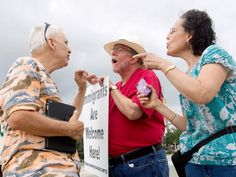 Immigration supporters David Smith, center, and Rona Smith debate with an anti-immigration protester on Saturday, Aug. 2, 2014, in Conroe, Texas. Texas Gov. Rick Perry plans to use $38 million in emergency funds to begin the deployment of up to 1,000 National Guard troops along Texas´ border with Mexico, his office said. Perry intends to use the Guardsmen to help law enforcement as a surge of people from Central America, including thousands of children, crosses into the United States. (AP…