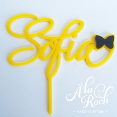 À la Roch Toppers are cut from high quality 3mm acrylic. This topper is solid yellow acrylic with a black bow accent. If you would like another colour please contact us for a quote. Small – up to 120mm wide, plus 50mm long stake Large – up to 160mm wide, plus 50mm long stake Custom sizes can be cut, please use the contact form for a quote. You can reuse your topper when handled with care, simply sponge the stake where the topper has been inserted into the cake, let it dry and place flat i...