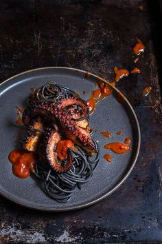 Grilled Octopus over Squid Ink Pasta and Tomato Garlic Sauce - spicy, garlicky, and frightfully delicious, this is the perfect Halloween night dish. Healthy game movie gluten free girls ideas date late carvings fight poker triva ladies guys friday burns h Grilled Squid, Grilled Octopus, Seafood Recipes, Cooking Recipes, Oats Recipes, Seafood Pasta, Shrimp Pasta, Restaurant Recipes, Sauce Recipes