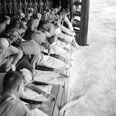 """Caption: """"U.S Navy sailors bury comrades at sea following two Japanese kamikaze strikes aboard the USS Intrepid (CV-11), an Essex-class aircraft carrier. On 25 November 1944..... two kamikazes crashed into the carrier killing six officers and fifty-nine crew.... Near the Philippines, en route to San Francisco, California, U.S.A. 26 November 1944. Image take by Barrett Gallagher."""""""