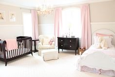 Pure white mixed with subtle splashes of pink in this large nursery unify the look, from linens on both bed and crib, to floor length drapes. Dark wood crib, table and dresser contrast over white carpet, with white wood bed frame on the right.