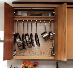 Hang your pans in a cupboard...It looks like a curtain rod and the hooks can move to make room for different sizes of pans. Genius!