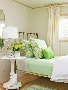 Loving this green and white room with the painted mirror and table. Love the rustic bed frame.