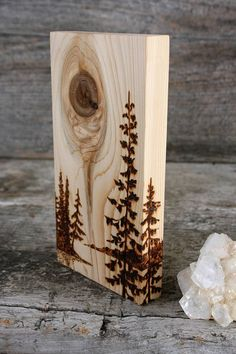 The wood grain and knot in this beautiful piece of wood inspired the landscape of pine trees and distant shores. I added some trees to work with the wood to create the artwork! All made by hand with a process commonly known as wood burning. The piece measures about 6 1/2 inches tall